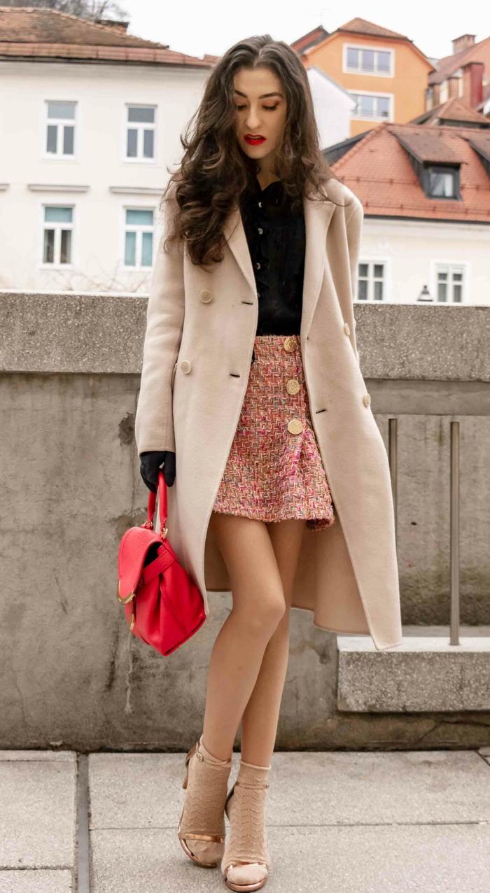 sac rouge, manteau crème et jupe avec boutons, chemise noire, cheveux noirs, femme aux longs cheveux chatains