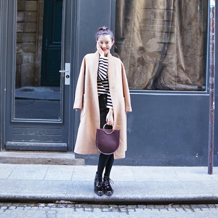 bottes noires, jupe courte, sac lilas, blouse rayée, manteau long rose poudré, chignon haut