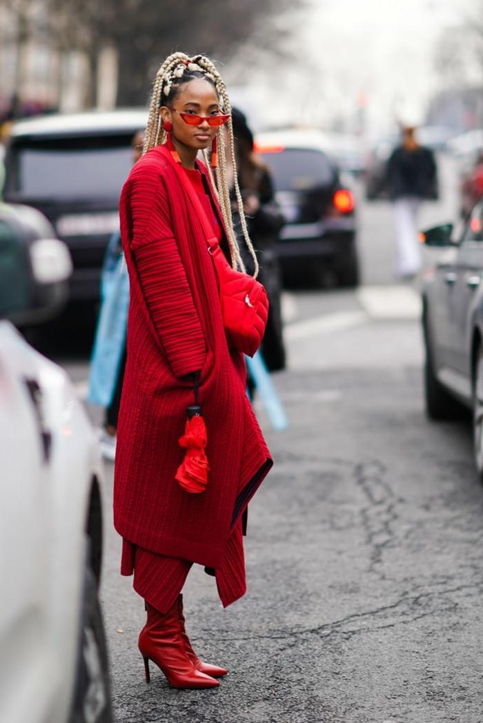 manteau long asymétrique couleur rouge, cheveux en tresses, lunettes oranges, bottes rouges