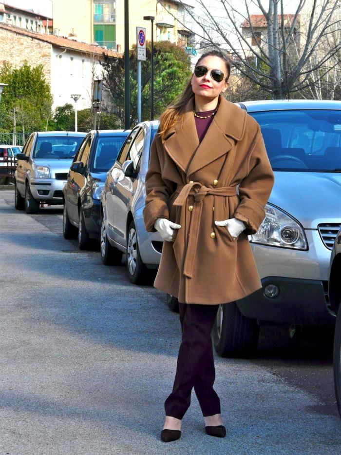 pantalon lilas, veste en laine couleur marron aux boutons, collier fin, gants blancs, escarpins