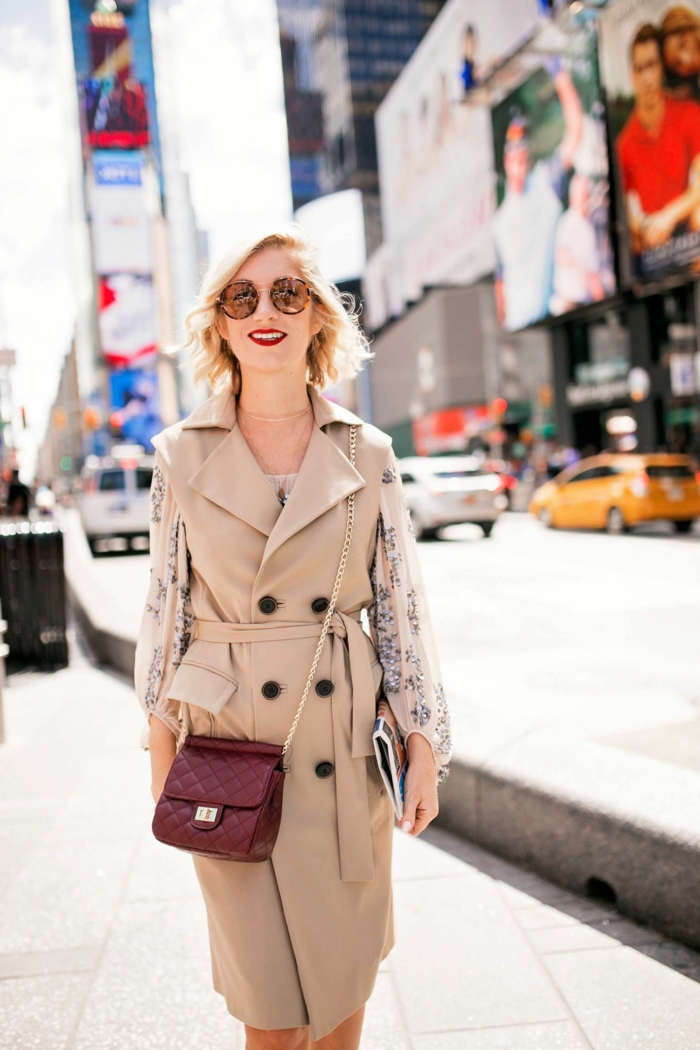 trench boutonné blanc cassé, sac burgundy, lunettes tendance, chemise en soie florale