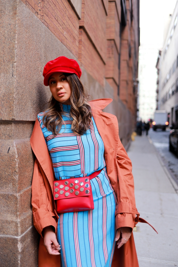 manteau trench, sac rouge, casquette rouge, robe bleue aux rayures verticales et horizontales