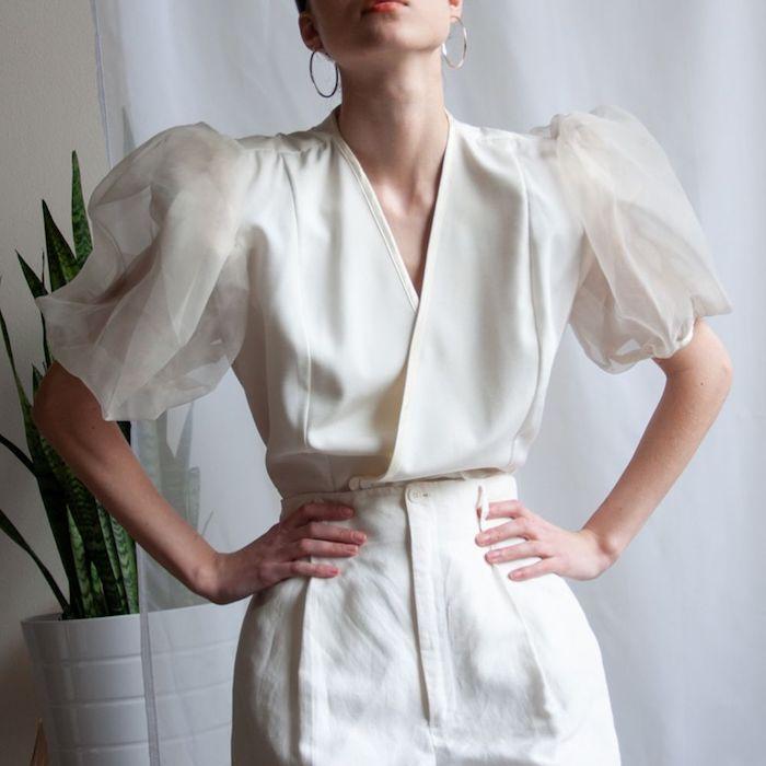 robe manche ballon en blanc une femme devant plant vert les mains sur la taille