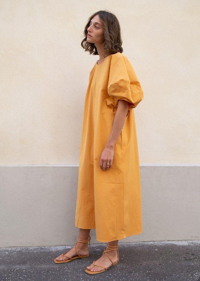 robe manches bouffantes taille large fille a cheveux mi long avec des sandales couleurs moutarde