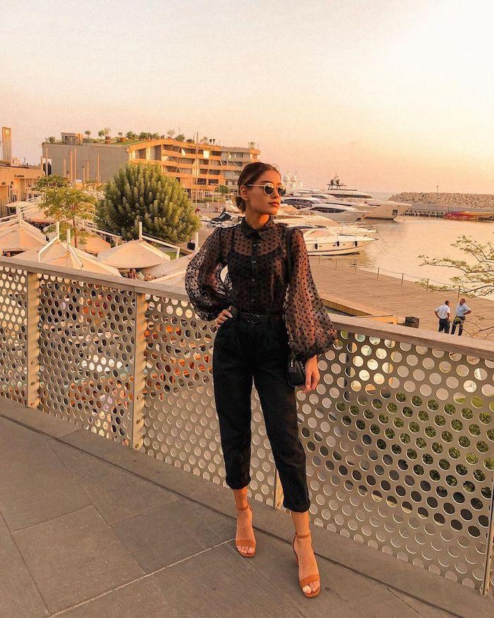 une femme devant la marine avec des lunettes de soileil et des chaussures a talon des vetements noirs et manches transparantes