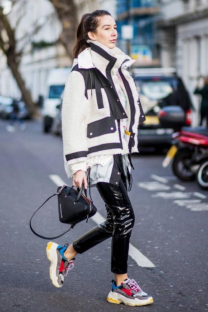 outfit streetwear femme pantalon cuir noir baskets multicolore sac à main noir veste blanc et noir