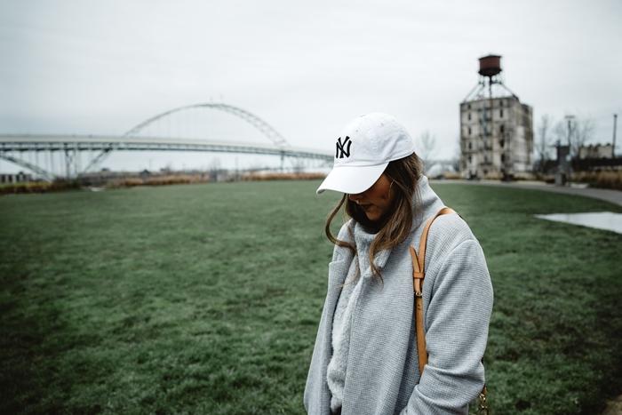 tenue d hiver femme sportive streetwear outfit manteau long gris pull streetwear large gris casquette blanche logo
