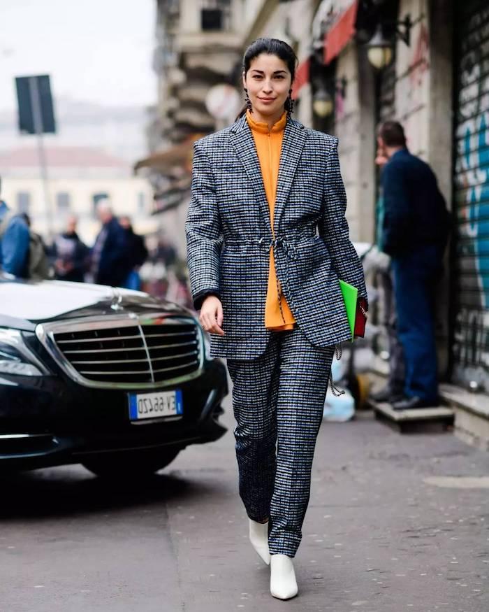 ensemble pantalon femme combiné avec une blouse orange et des bottes blancs