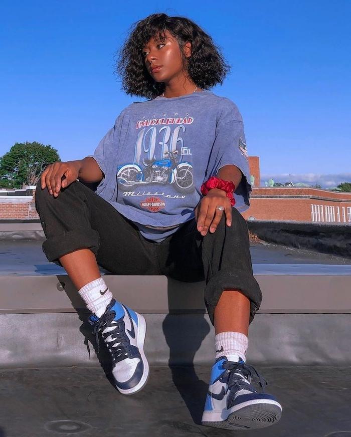 tenue de sport femme tendance des baskets nike avec un pantalon sportif et un t shirt enorme une fille assise