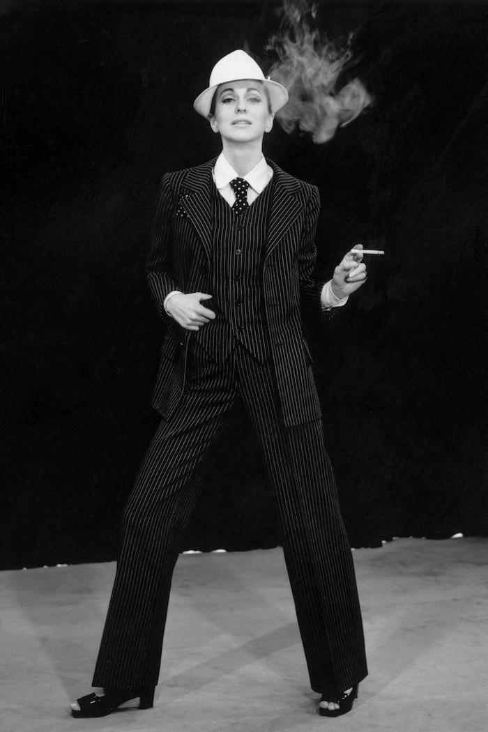 une femme qui fume cigrette vetue en en smoking a rayures avec un chapeau a bordure