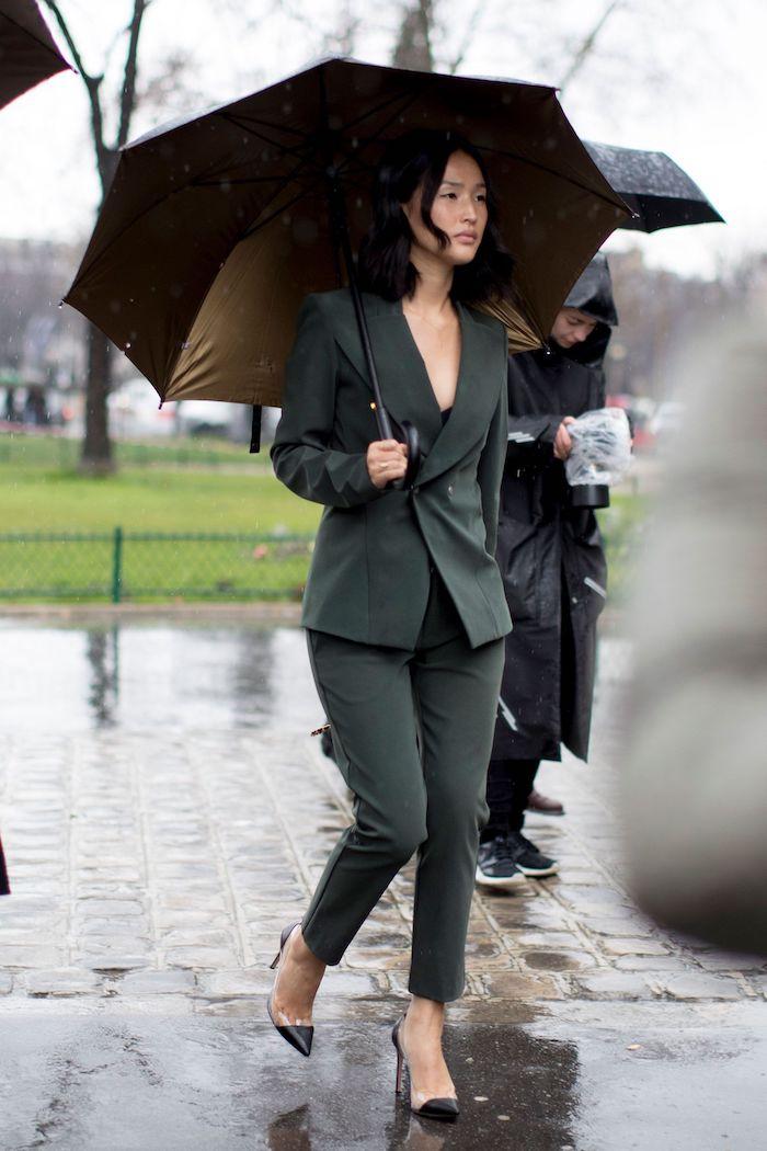 une femme qui porte un tailleur avec longeur au dessus des chevilles et porte un parapluie
