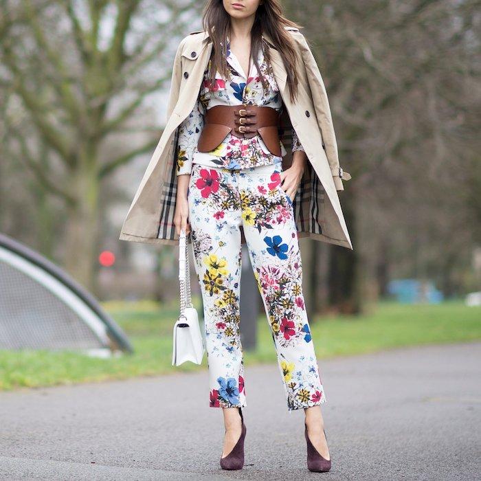 une femme vetue en ensemble tailleur chic aux motifs floraux avec une ceinture large en cuir et manteau burrbery