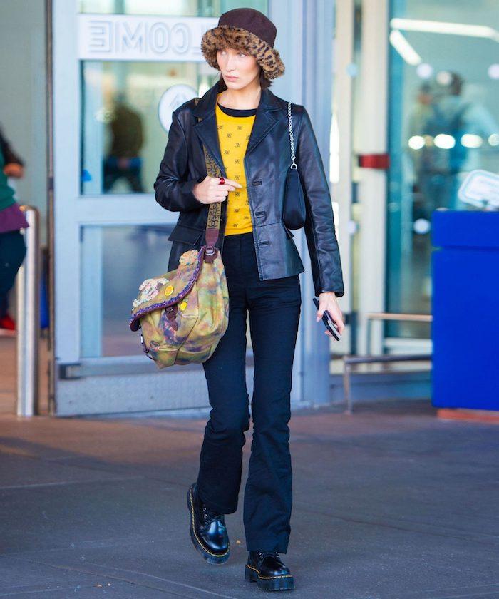chaussure style doc martens bella hadid a l aeroport avec un chapeau fedora leopard et une blouse jaune