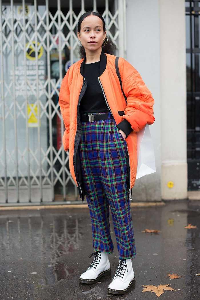doc martens blanche avec un pantalon a carreaux bleus et verste orange