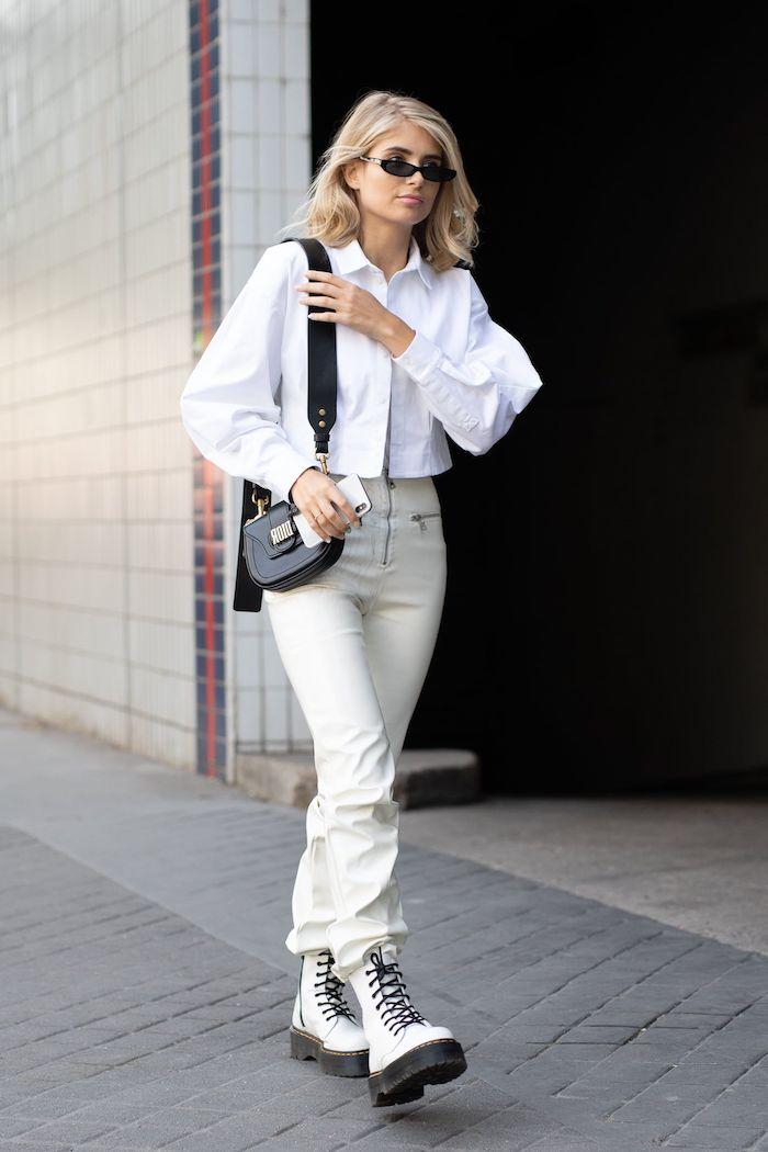 doc martens blanche une femme vetue en chemisier blanc avec un sac en cuir noir