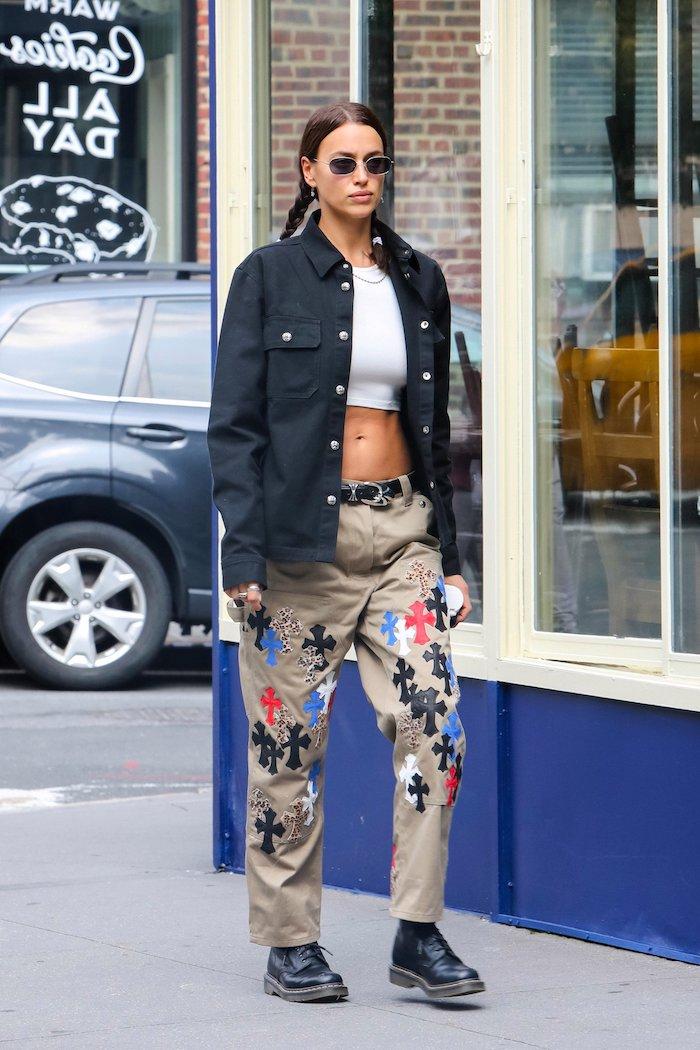irina shayk avec des chuassures doc martens une chemise ample et pantalon biege a motfs croix