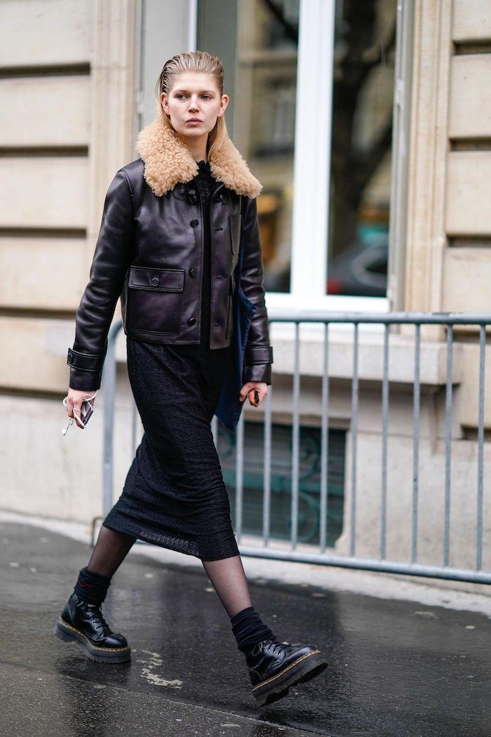 look doc martens avec une veste en cuir et col au fourrure jupe mi longue et un collant noir