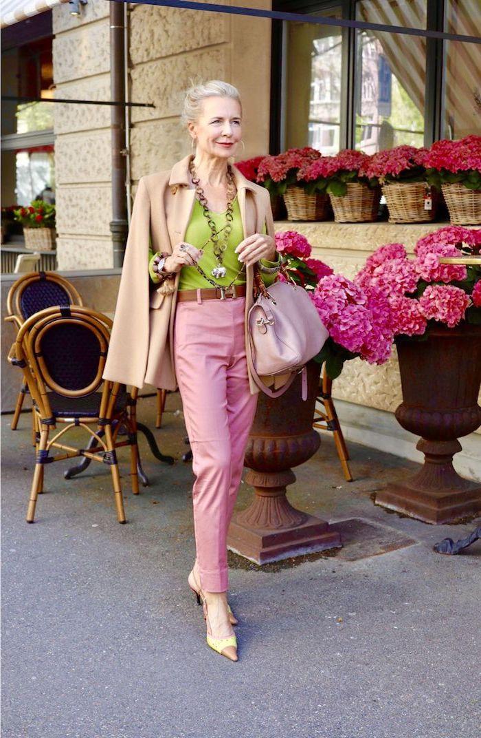 pantalon rose chemise verte manteau beige sac à main rose collier original look coloré femme 60 ans