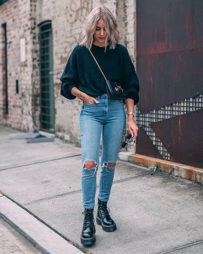une femme avec jean déchire pull noir et des bottines style doc martens