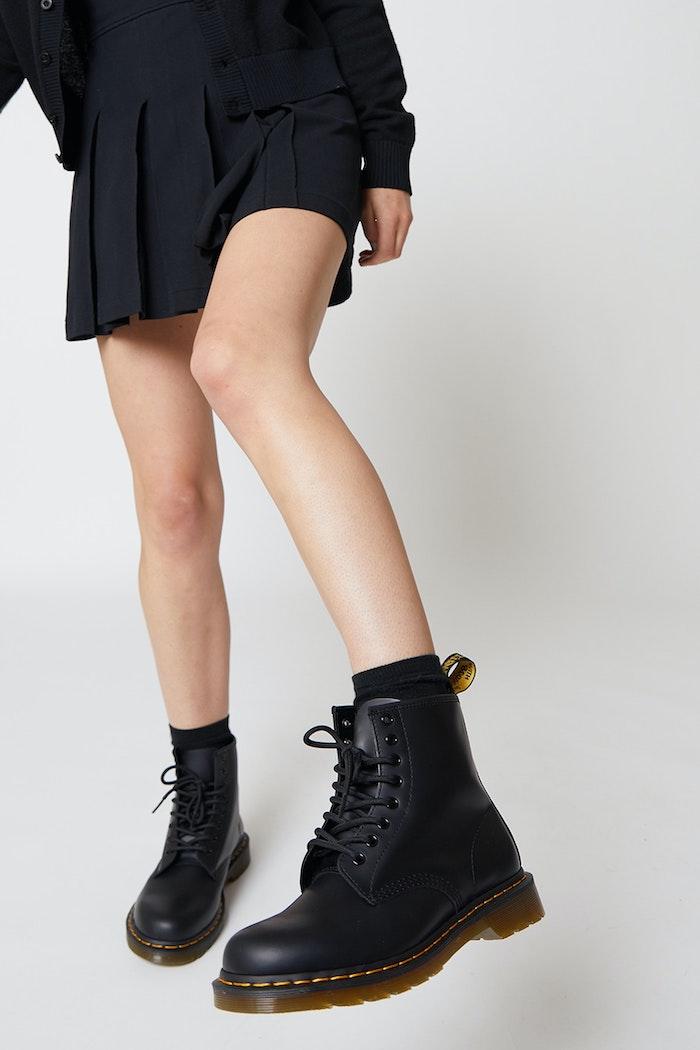 une femme en jupe plissée noire et des bottines doc martens