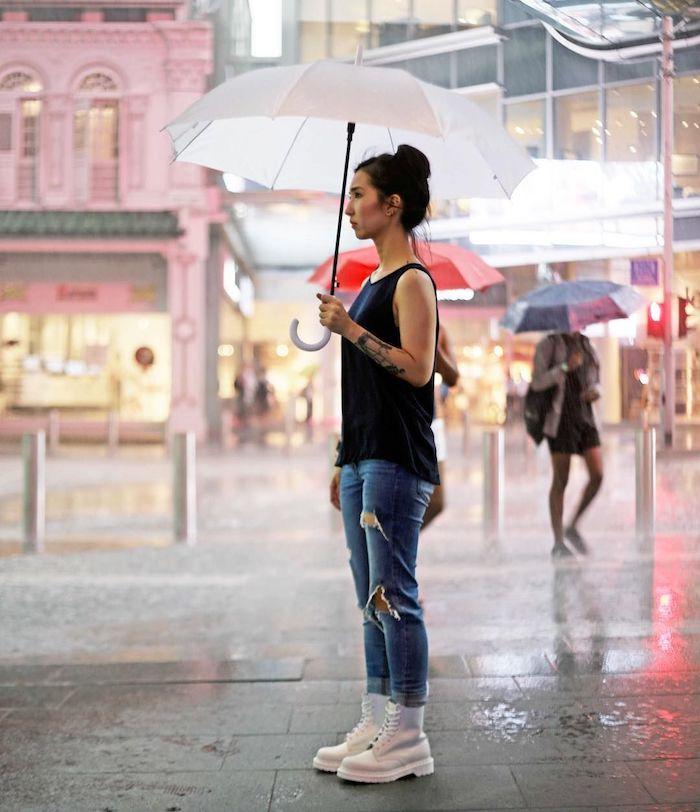 une femme qui tient une parapluie vetue en jean déchiré et top noir