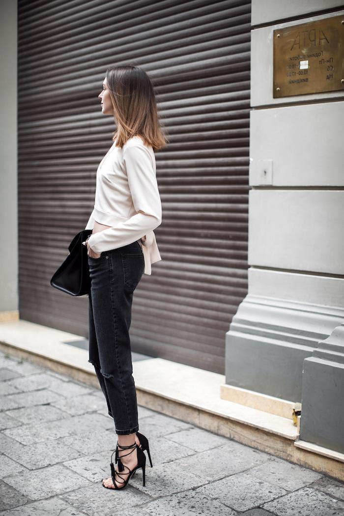 jean mom noir avec une)blouse chic et des sandales aux petites courroies une femme devant une porte fermé