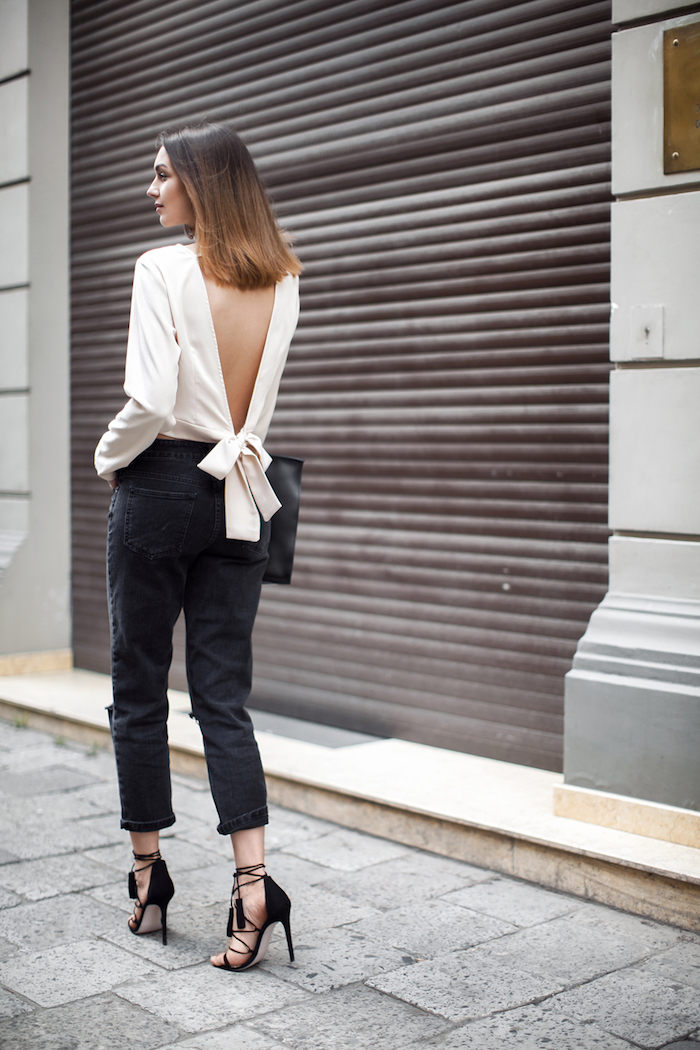 jean mom noir combiné avec une blouse chic beige le dos nus et des sandales