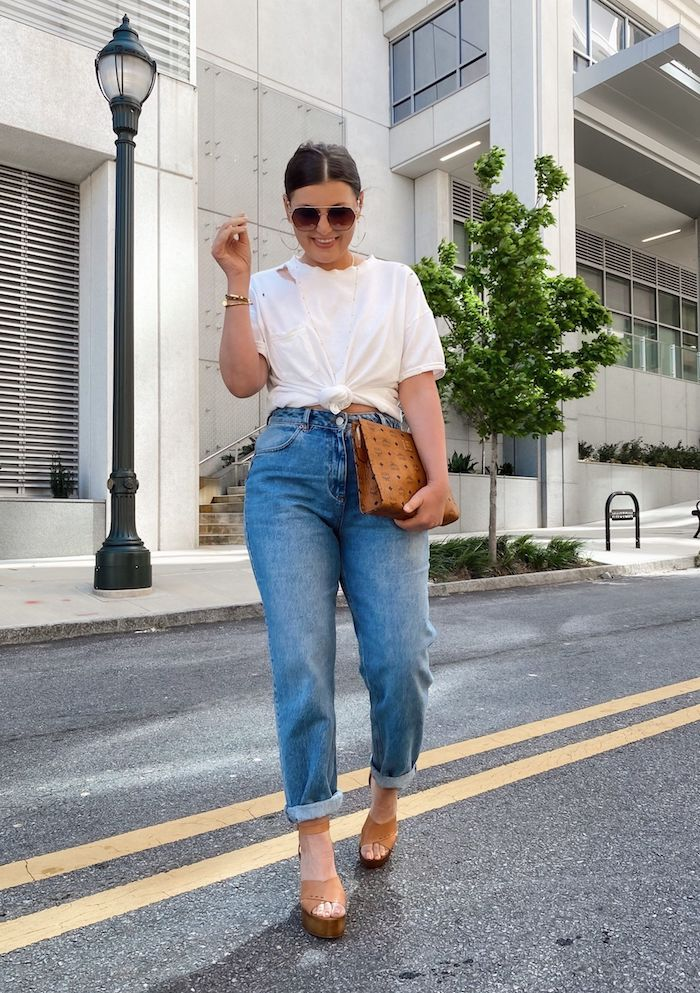 jean mom pour quelle morphologie une femme vetue en t shirt blanc noué un sac a main en cuir et des sandales beiges