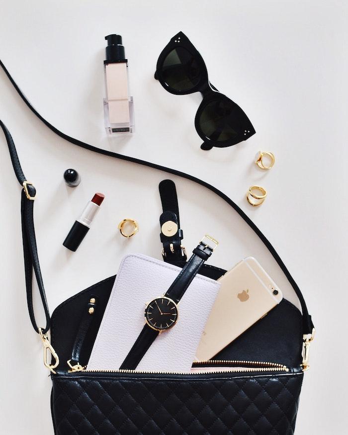 le contenu d un sac parsemée inclut de maquillage un montre portable et des lunettes a soleil