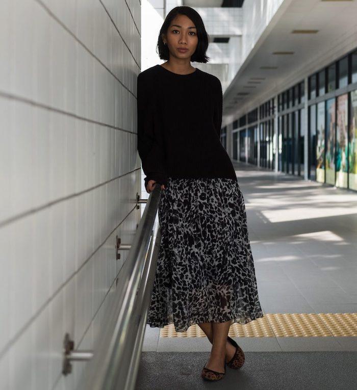 tenue classe femme avec un pull noir tricotée et une jupe midi aux imprimés