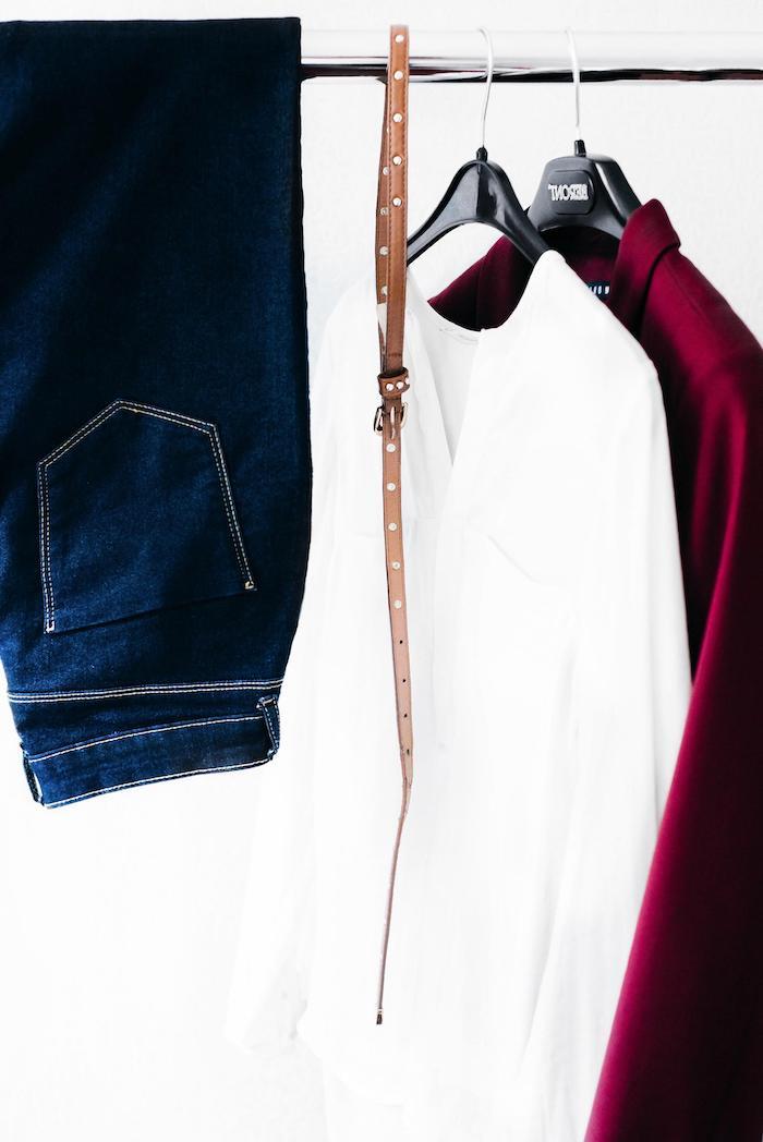 un jean chemisier blanc et veste bordeux sur des cintres garde robe minimaliste