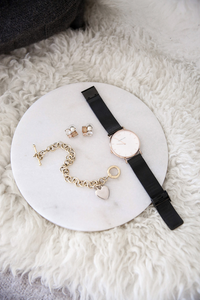un montre et bracelet dorée sur un plateau ronde posé sur un tapis blanc accessoires style minimaliste