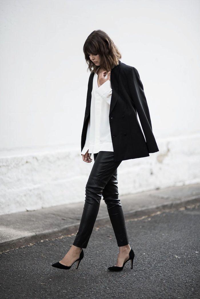 une femme en tenue style qui comporte pantalon en cuir chemisier blanc et une veste noir