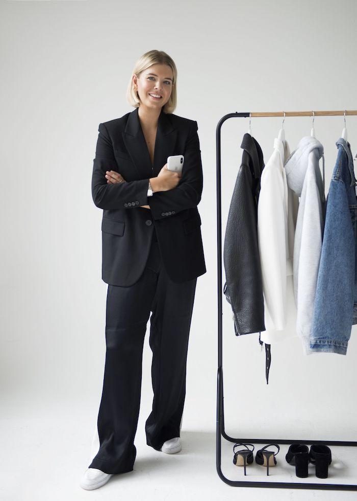 une femme vetue en tailleur noir classique e coté d un porte manteau ou garde robe minismaliste