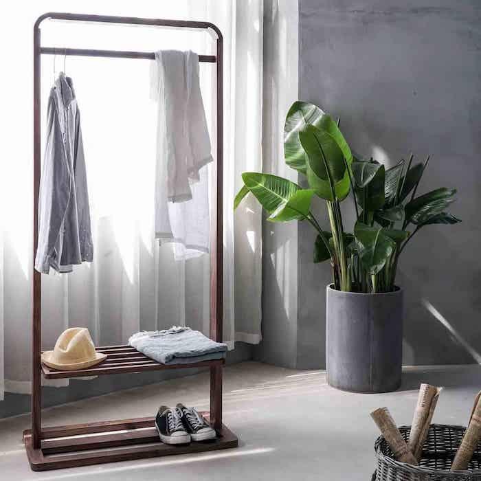 une garde robe minimaliste avec une plante verte a coté et chemise accroché au porte manteau