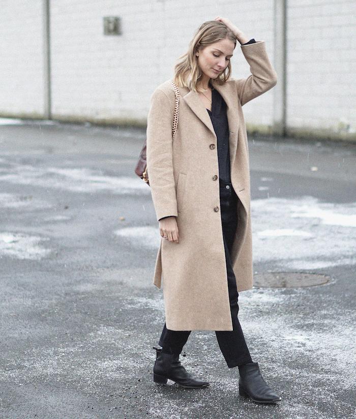 une idée tenue femme en style minimaliste avec un manteau longue beige et des bottes en cuir noires garde-robe minimaliste
