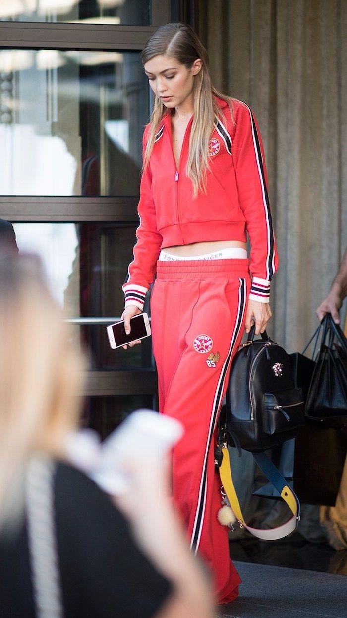 gigi hadid en marque streetwear d un survetement rouge et un sac a dos en cuir