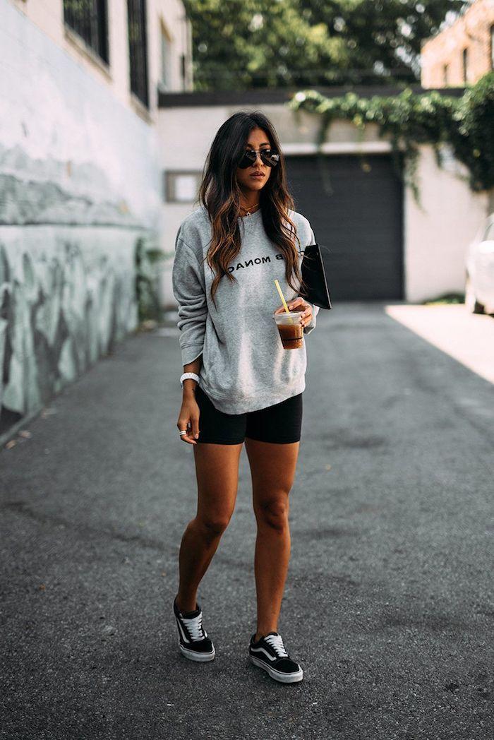une femme porte marque américaine des baskets vans un short noir et blouse gris