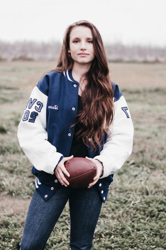 une femme vetue en jean foncé et une veste américaine qui tient une balle de rugby