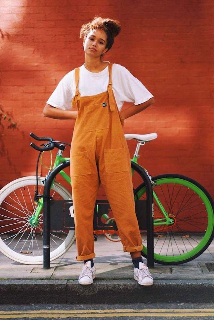 Salopette orange adorable, fille chignon haut, bicyclette verte, mur orange en briques, pantalon femme chic, habillé pantalon à pince taille haute