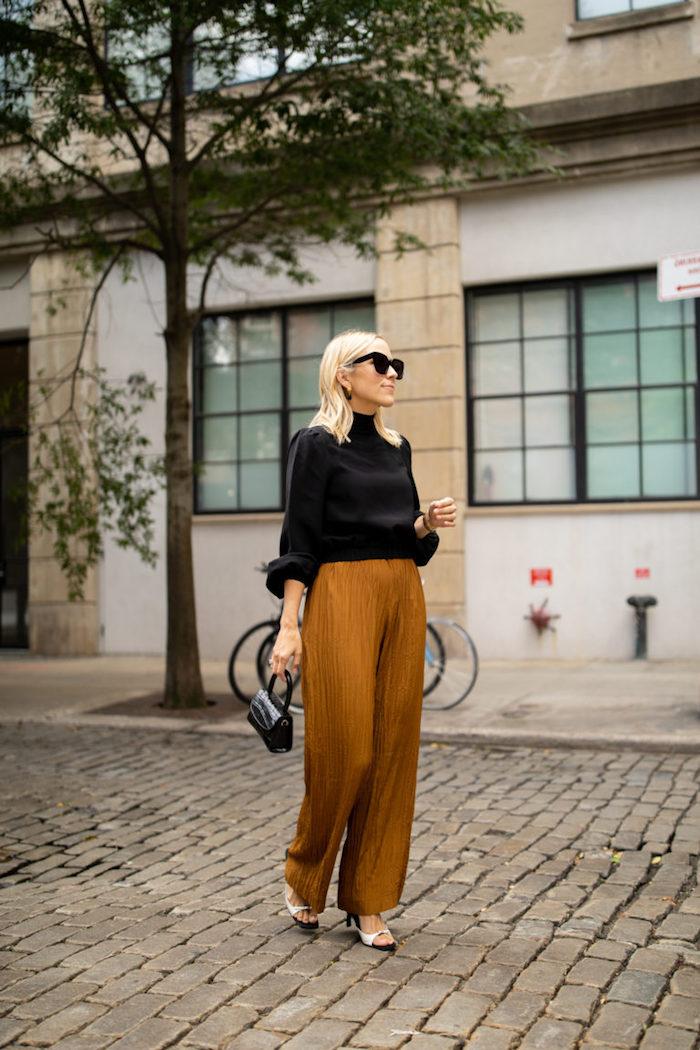 Photo inspiratrice de tenue de jour femme en automne, idée pantalon évasée et t-shirt manche longue noire, lunettes de soleil modernes