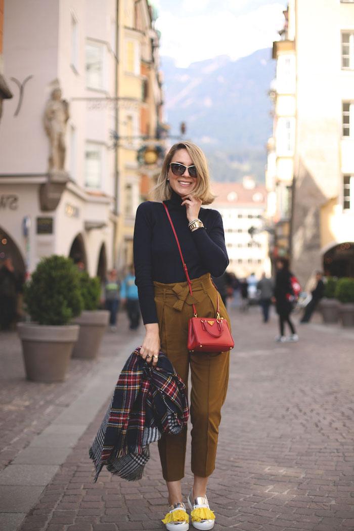 Femme blonde coupe carré, lunettes de soleil modernes, pantalon a pince femme, tenue avec pantalon femme chic avec sac débardeur rouge cuir